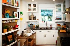 Eclectic Kitchen. Love the burlap on the shelves on the left. Dark counters, white cabinets, colorful accessories.