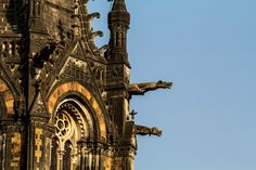 Fantastic protruding gargoyles adorn the spires atop the Chhatrapati Shivaji Terminus (CST) at Mumbai, Maharashtra. The CST, also known as Victoria Terminus (VT), is a UNESCO World Heritage Site notable for the fusion of high Victorian Gothic architectural style with motifs of India, notably its flora and fauna. The gargoyles also serve as waterspouts with visible pipes in their open mouths.
