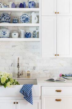 white cabinets, blue accessories, marble tile backsplash