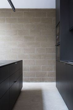 Industrial materials were exposed and celebrated in this home with black MDF for the kitchen, concrete and exposed blockwork.