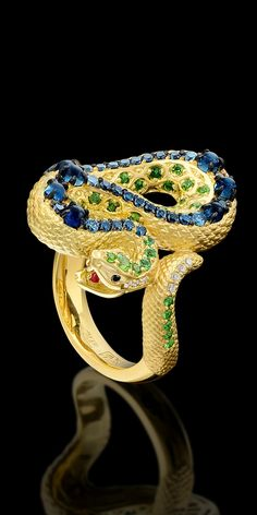 From the Animal World Collection: 18K yellow gold ring with white, black & blue diamonds, tsavority, demantoids, tourmalines, and rubies.