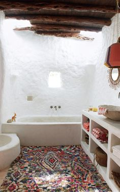A cozy bathroom featuring Spanish obra (built-in cement cabinets), a patterned rug, and a lampshade by Ana Kraš | Telegraph