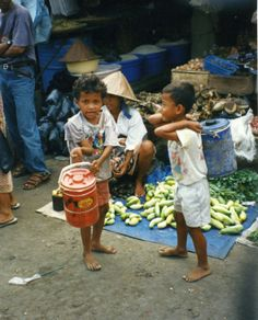 Two boys with food buckets at the market on Sumatra, Indonesia.  Sumatra, is an island in western Indonesia, to the west of the Sunda Islands. It is the largest island that is entirely in Indonesia and the sixth largest island in the world.