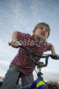 Young boy making face on bicycle - Stock Photos