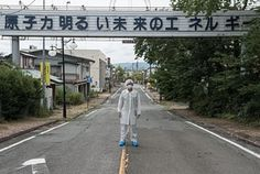 "The photographer Arkadiusz Podniesinski stands on one of the main streets of Futuba, a Fukushima village. The writing above him says: ""Nuclear energy is the energy of a bright future""."