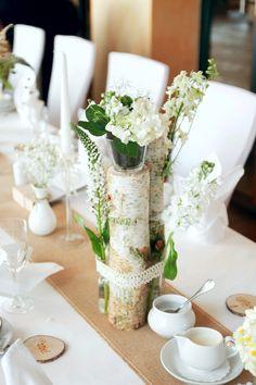 Das Centerpiece der Dekoration besteht aus drei Birkenholzstämmen, die mittig mit weißem Spitzenband zusammengehalten werden. In die Zwischenräume werden Reagenzgläser mit Blüten gesteckt. Obenauf befindet sich ein kleines, filigranes Blütengesteck. --- Birke, Vintage, Jute, Spitzendeckchen --- designed by www.tischleinschmueckdich.de