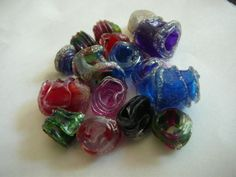 Recycled Plastic Bottle Beads | Made by cutting bottles into strips (one end pointed, for a nicer finish), coloring them with permanent marker, rolling them up and melting them plastic with a lighter. (Held using jewelry tools.)
