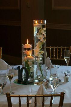 Wedding photography: centerpieces-submerged flowers and floating candles. DIY table numbers