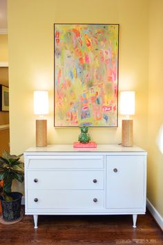 Love this white cabinet with such colorful art in a simple frame