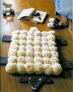 Pompom sheepskin rug (instructions in Italian).  Felt and glue will work for the black parts if you don't knit or crochet.