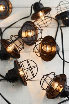 """Metal Lantern String Lights. 10 lights enclosed in black metal caged lanterns. Can connect three together to create a grand display above an outdoor wedding dance floor. Indoors or outdoors. Strand has a lighted length of 9' with 6"""" of cord at either end. Lanterns 3.5"""" tall."""