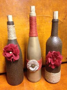 Our Pink Burlap Bliss Wine Designs feature handmade burlap flowers with pearl-inspired centers and sand and pink colored twines to adorn the necks.