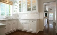 Amazing butler's pantry design with white glass-front shaker kitchen cabinets, marble counter tops & backsplash, bridge kitchen faucet and bamboo roman shade.