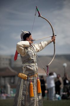 A female Mongolian archer in elegant traditional dress competes in the Naadam Festival, Mongolia, held in July each year. She is aiming to topple a small wall of marked blocks from over half a football field away.