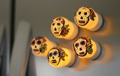 "Day of the Dead Magnets--Day of the Dead or Dia de Muertos is a holiday celebrated throughout Mexico and other countries around the world. Traditionally, a skull or ""calavera"" (in Spanish) is decorated to help celebrate the day. Turn ping pong balls and battery tea lights into ""Sugar Skull"" magnets for a great way to open up a dialogue with kids about holidays celebrated in other countries."