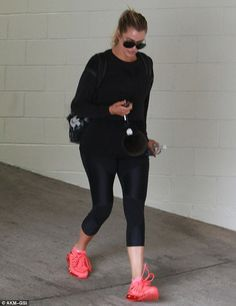 She's a sport: The TV star highlighted her toned curves in tight gym wear which consisted of black lycra leggings and a matching cropped sports top with a vest underneath