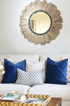 Cobalt accent pillows and a mixed media sunburst mirror adds just the right amount of style to this welcoming living room!