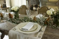 This can easily be re-created at home with a few olive branches and small arrangements of white roses.