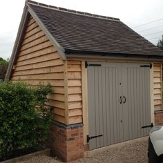 Oak frame garage, larch cladding and brick plinths, farrall and ball paint work. - Oak frame garage, larch cladding and brick plinths, farrall and ball paint work. By R J Heathcote. Garage Door Framing, Timber Frame Garage, Wooden Garage Doors, Garage Door Design, Wooden Garages, Best Garage Doors, Garage Shed, Wooden Car, Larch Cladding