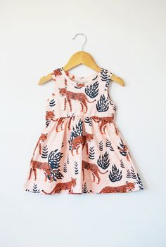 By popular demand, we are so excited to be able to offer this sweet little dress! It is made up of our awesome safari tiger print on 100% organic cotton knit. It pulls on easily over the head. Not only is it stylish but its super comfy to boot!  This dress features cotton produced in the USA that is certified organic by global organic textile standards so you can feel good about dressing your baby in it! We serge all seams for added durability and strength. Here are our approximate sizing…