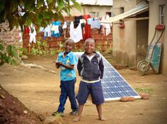 Africa's Mobile-Sun Revolution - Solar panels are a part of the landscape in southern Africa. Here, two boys ham it up for the camera while playing around a large-form factor panel.