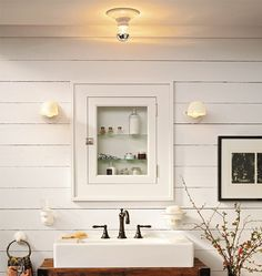 Perfect for bath off the mudroom  White and white bathroom with tongue and groove walls, white sink, white medicine cabinet with clear glass.