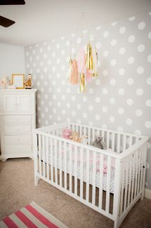 Grey wall with with polka dots as backdrop for this darling nursery . Style Me Pretty