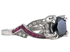 Edwardian style double pronged Platinum setting. It has two interweaving rows of Princess cut Burma rubies 0.48ct and pave set diamonds 0.20ct. There are also diamonds and filigree work along the base of the center stone. This four pronged setting can accommodates 1.69ct Black Diamond