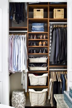Super organized closet with metal baskets with canvas lined metal hampers, shoe shelves, woven storage baskets and black & white garden stool...perfect for the husband's closet