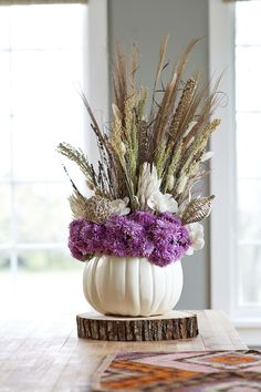 Turn a pumpkin into a vase by carving a circle in the top and scooping out the insides. Fill with floral foam that's been soaked in water, and arrange a mix of grasses and flowers. To prevent shedding, give the arrangement a light dusting of inexpensive aerosol hairspray.