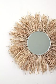 How to make this raffia-fringe round mirror, a take on the ever-popular sunburst mirror trend! It also gives an African juju hat vibe decorations diy Make this Tropical-Inspired Raffia Sunburst Mirror