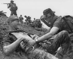 South Vietnamese and Montagnard troops attack in an uphill battle near Ha Thanh, some 325 miles northeast of Saigon, Sept. 2, 1968, as an American medic attends a wounded U.S. Special Forces soldier. The GI was wounded during the battle as an Allied strike force sought to retake an outpost which had been overrun by the Viet Cong on Friday. The strike force retook the outpost. (AP Photo)