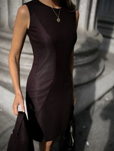 fashion blogger wearing a burgundy red hugo boss suit dress with black stiletto jimmy choo pumps and gold hoop earrings holding hugo boss suit jacket
