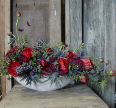 The check in table will have a wooden box filled with red ranunculus, blue thistles, blue privet berries, purple astrantia and seasonal greenery.
