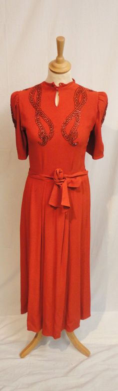 Orange Crepe Dress with short sleeves and beaded circular detailing to the shoulders, with a pleated skirt and tie waist, circa 1940's.