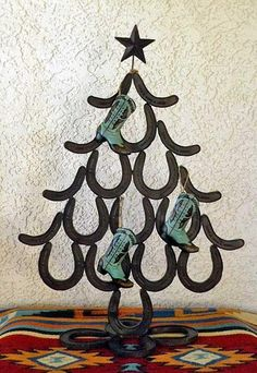 This adorable tree almost a sculpture. Hand made from soldered tin it has a rustic finish and wonderful detail. This makes a great dramatic centerpiece. x each horseshoe is x Shown Horseshoe Christmas Tree, Western Christmas, Christmas Crafts, Christmas Decorations, Christmas Horses, Xmas, Holiday Decor, Horseshoe Projects, Horseshoe Crafts