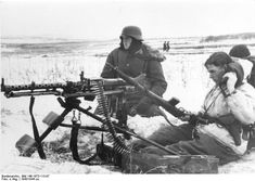 "Men of the Waffen SS ""Totenkopf"" Division man a MG 34 in the open steppe, Note the two troops casually strolling in the right background"