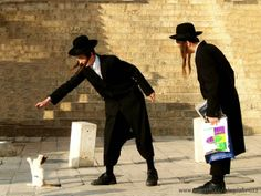 Two Orthodox Jews, playing with a street cat in Jerusalem, Israel © zbrazz_wang