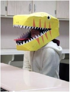 Halloween Dinosaur Costume: Be creative make the dinosaur head by using spare shoe boxes. Take 2 shoeboxes. Remove both the lids and take the remaining two boxes. Place one on top of the other with open ends closing each other. Insert one box into another just an inch or 2 on one side making a V shape. Now, this will act like the head of the dinosaur. Stick eyes on the top and teeth to the side of the box.  Make a body and tail, similarly with things around in your home.