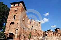 Photo made in Verona in Veneto (Italy). The city of Verona, known as the site of the tragedy of Romeo and Juliet, has been declared a World Heritage Site by UNESCO for its urban structure and its architecture. The picture shows a part of the walls of the medieval castle with the tower in the foreground it's on the door of one of the entrances to the castle. The MRA silhouetted against the blue sky with small white clouds.