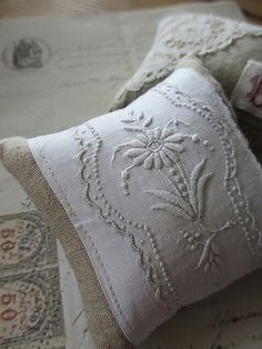 Wrap a neutral pillow with vintage embroidered linen table runner or dresser scarf.