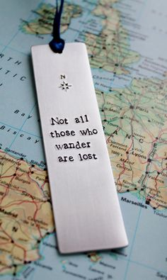 This is a hand stamped bookmark created by me! It says: Not All Those Who Wander Are Lost and has a compass design at the top of the bookmark It is by and is made from thick aluminium. Creative Bookmarks, Diy Bookmarks, Corner Bookmarks, Custom Bookmarks, Bookmark Craft, Lotr Quotes, Bookmarks Quotes, Watercolor Bookmarks, Book Gifts