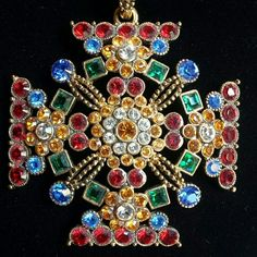 """'Joan Rivers' Crystal Maltese Cross Necklace 'Joan Rivers Classics Collection' brightly colorful crystal Maltese Cross. Perfectly inlaid crystals of vibrant red, blue,  green, amber, and clear decorating a goldtone 2.5"""" X 2.5"""" Maltese cross pendant. The beauty goes on with the 29"""" crystal bead necklace which has all mentioned colors and purple as well! Lobster clasp closure with an additional 4"""" chain extender. Both necklace and pendant have the Joan Rivers signature. Comes with black velvet…"""