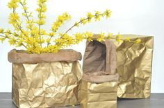 I love the idea of taking basic paper bags, spray painting them gold, and rolling over the edges. These make the perfect gift bag.