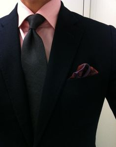 Nice combination of a Dark gray textured tie. Light pink shirt. And complimenting pocket square