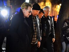 Members of the band U2 pay their respects and place flowers on the pavement near the scene of yesterday's Bataclan theater terrorist attack in Paris, France.  Jeff J Mitchell, Getty Images