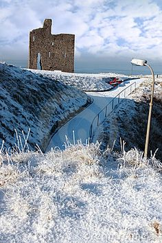 A seasonal snow covered view of Atlantic ocean and Ballybunion Castle
