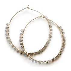 Handmade hoop earrings are wire wrapped with glittering, faceted labradorite gemstones. Available in 14 karat gold-filled or .930 Argentium silver in two stock sizes: Medium - 1.5 inch (3.18 cm) diameter Large - 2 inch (5.08 cm) diameter Custom sizes and solid yellow or white gold are available on request. Please contact us for a quote.
