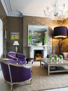Purple hue living room and elaborate chandelier, very formal wall covering, oversize floor lamp with **purple shade** make this room stand out and make a bold statement. A comfortable looking room.
