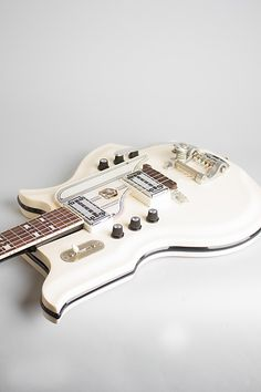 National Glenwood 98 Model Solid Body Electric Guitar (1964), made in Chicago, serial # G-37688, white finish, molded Res-O-Glas body, maple neck with rosewood fingerboard, original black hard shell case. The still-dazzling National Res-O-Glas guitars of the 1960s remain some of the most exubera...